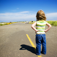 Child standing alone in a road looking at the horizon